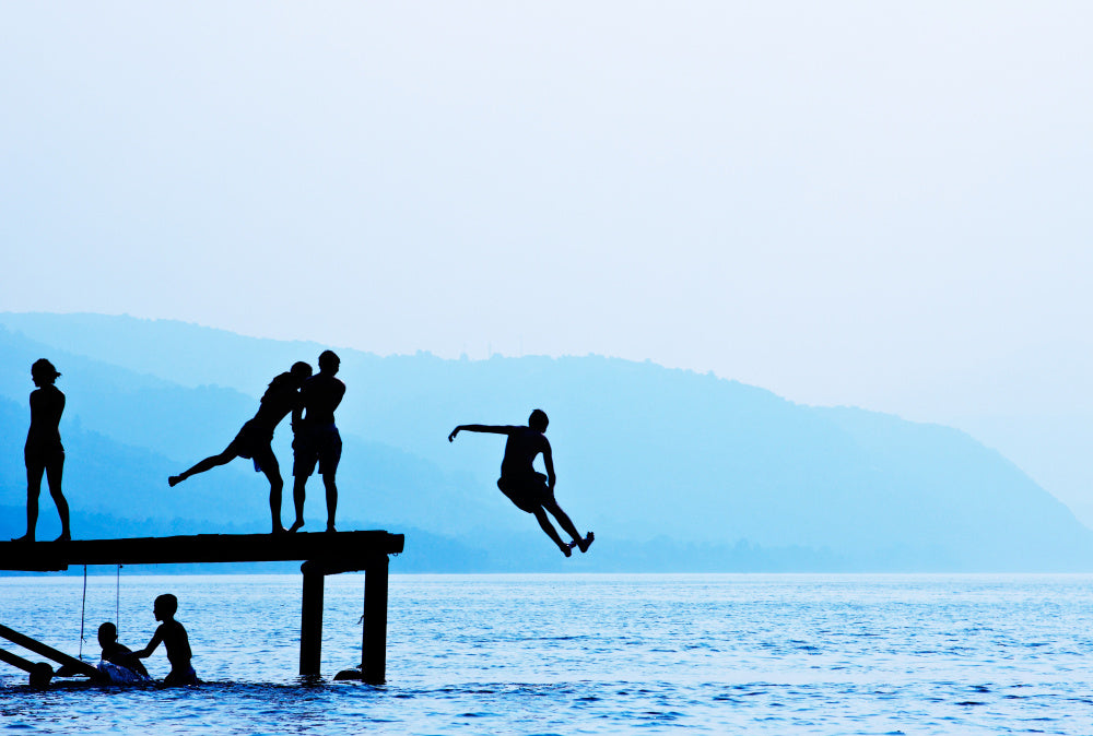 Silhouettes of a group of friends jumping off a dock into the water