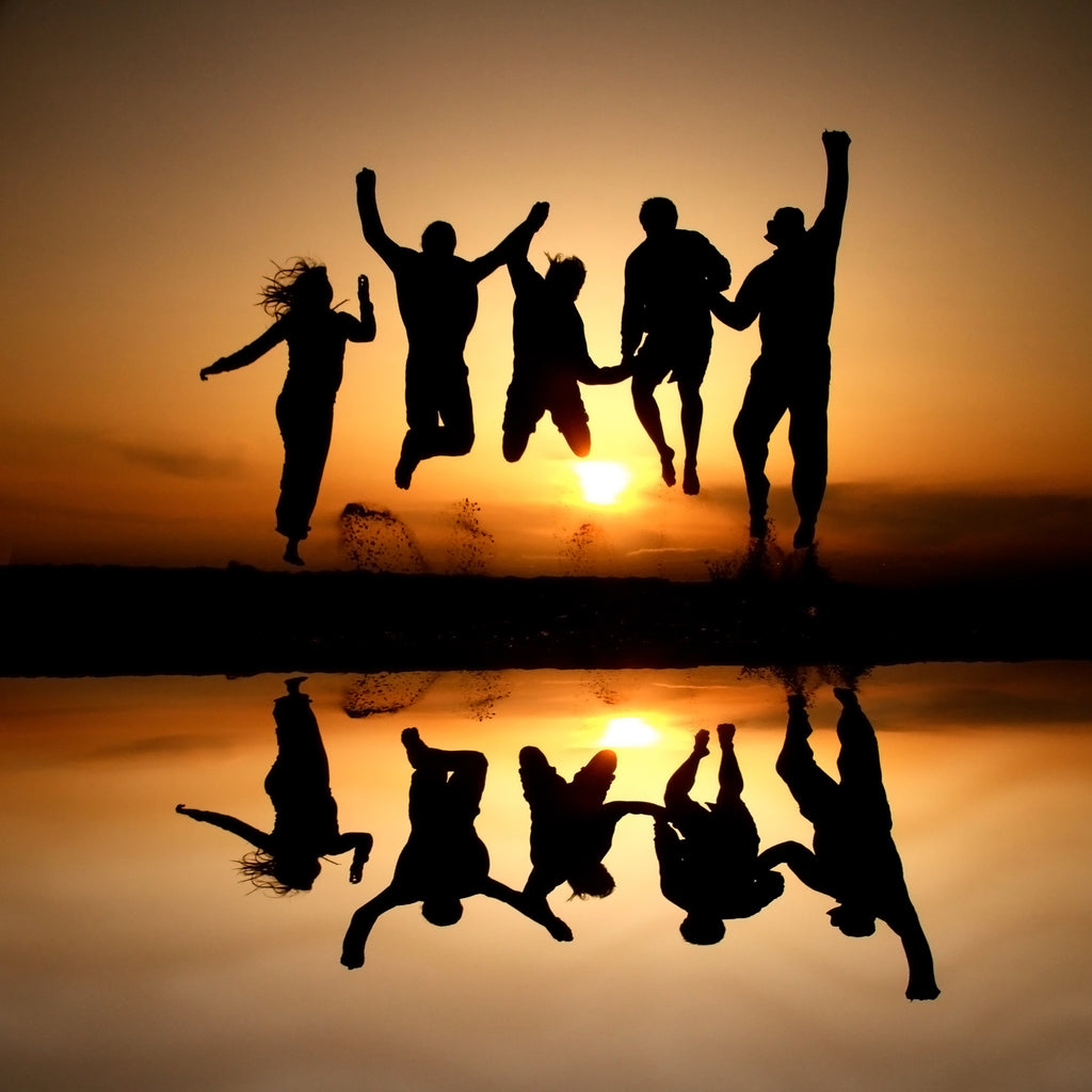 Silhouette photo of a group of friends jumping in the air at the beach having fun at sunset