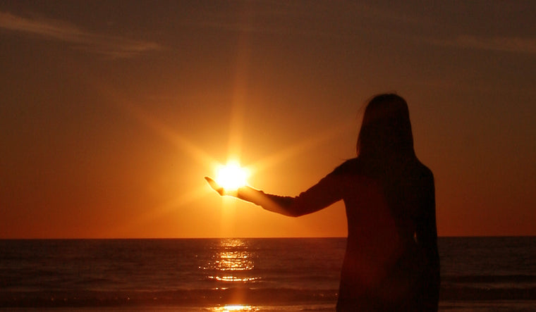 Forced perspective photo of a person holding the sun in their hand during a sunset