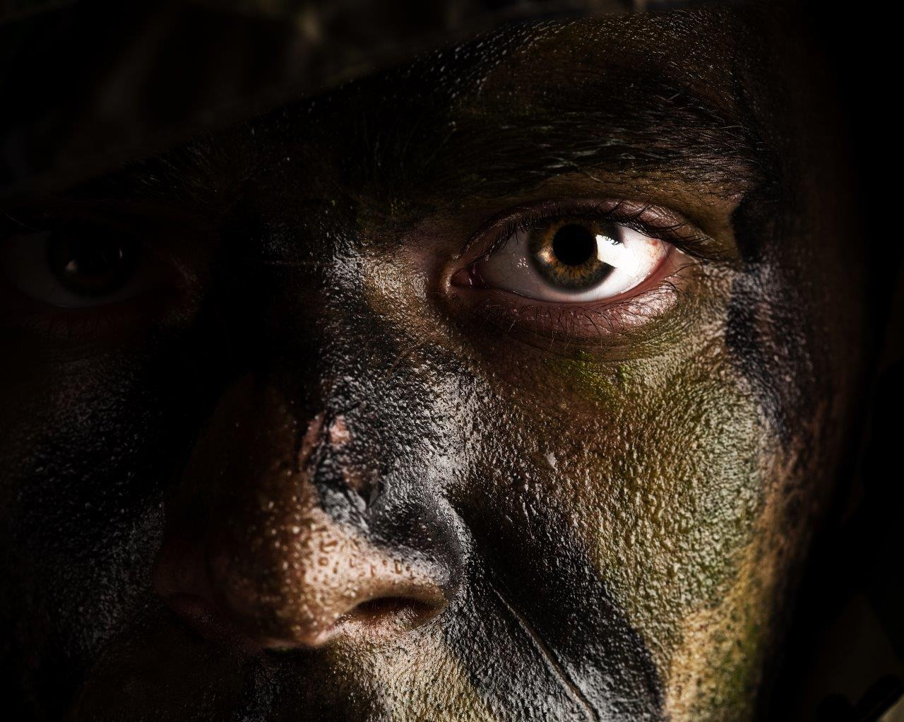 Close-up portrait of a man wearing camouflage face paint