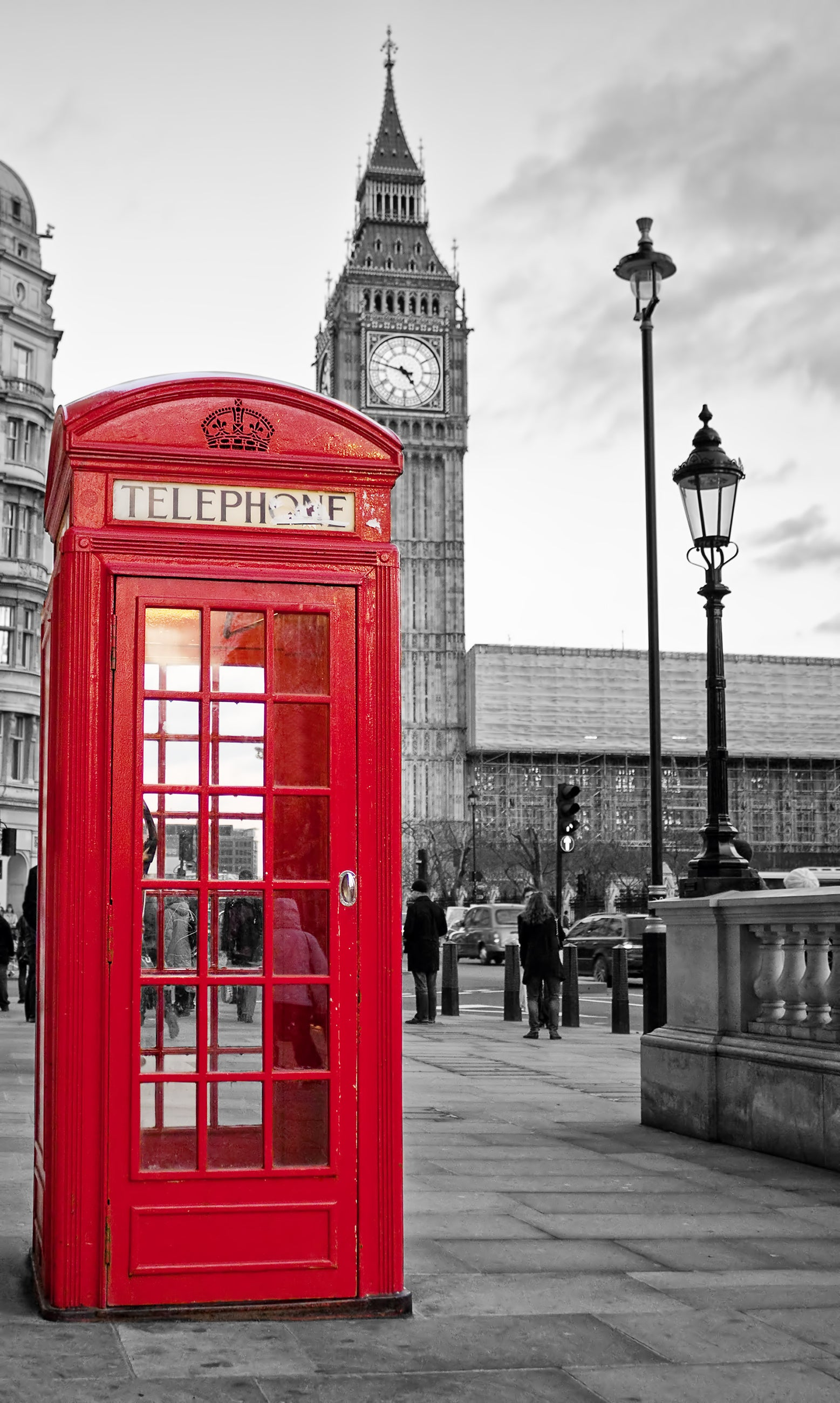 Traditional red phone booth in London with Big Ben clock tower in the background