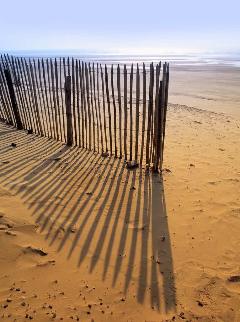 An old wooden fence and its shadows on a sandy beach