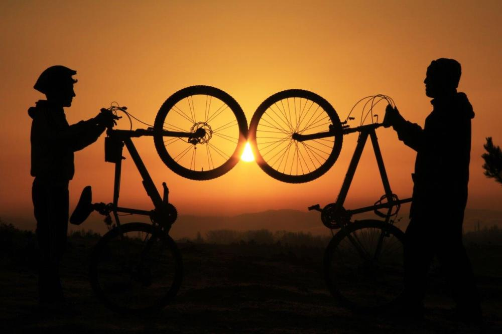 Sunset silhouette of two people holding up their mountain bikes