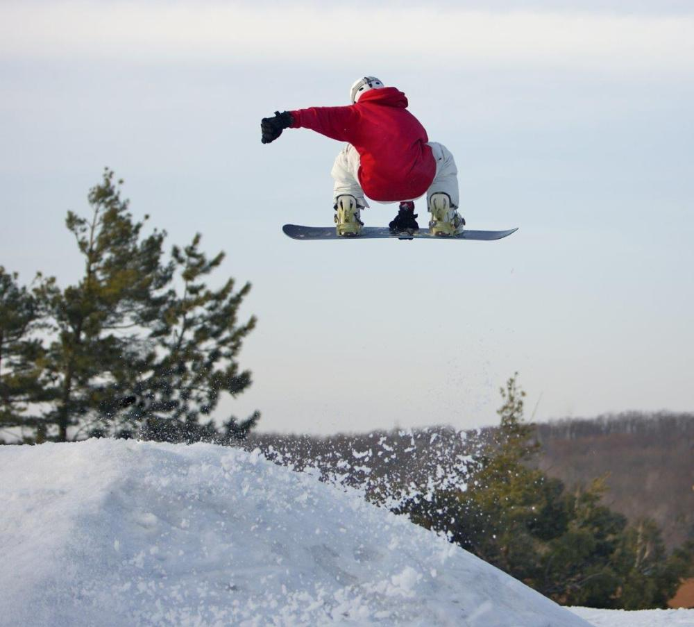 Snowboarder in the air with their arm illustrating the use of horizontal leading lines in photography