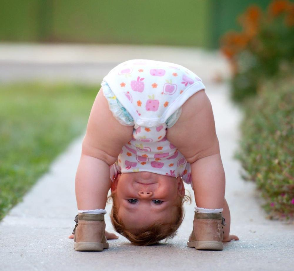 Little girl trying to stand on her head, peering through her legs