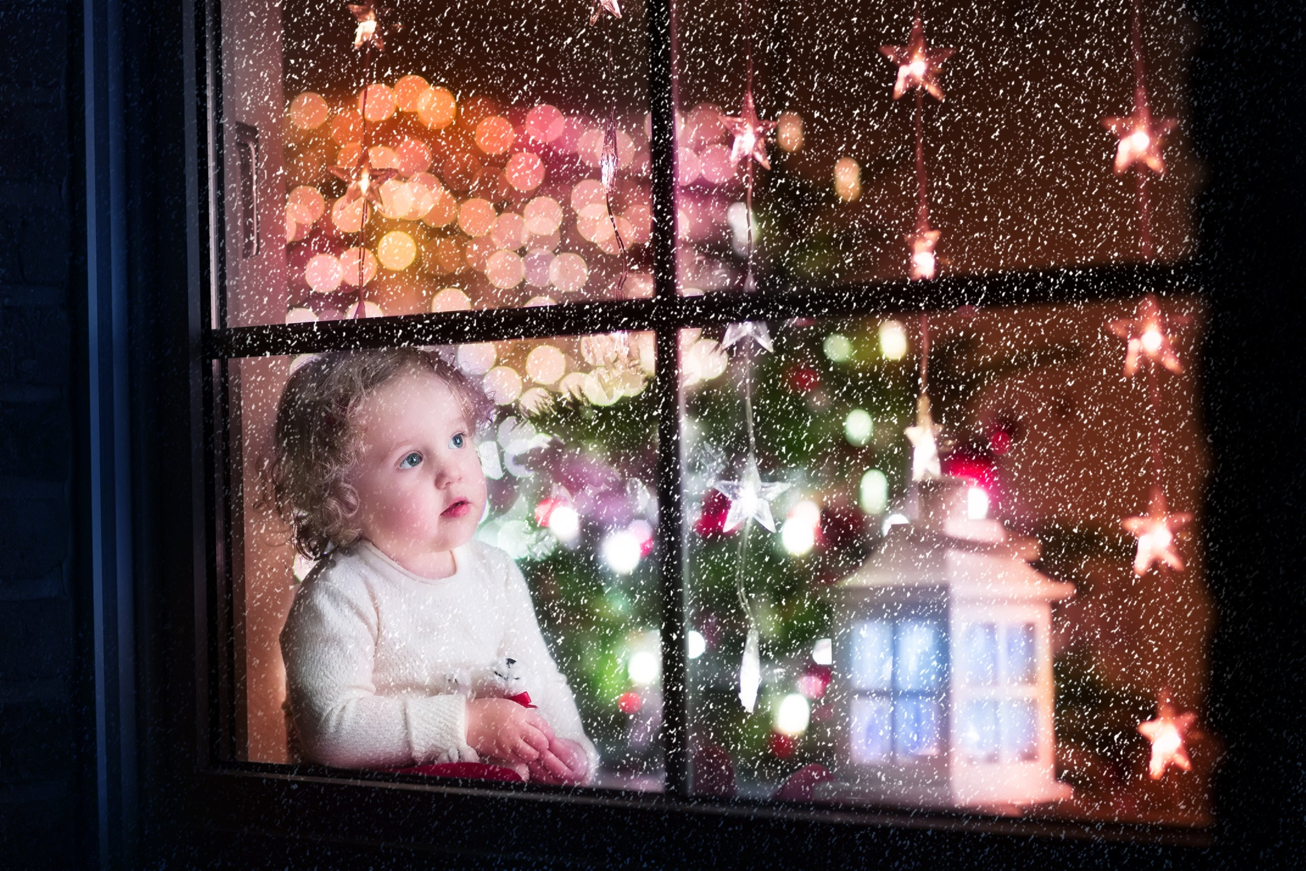 Young child looking out the window at snow on Christmas Eve - example of holiday photography