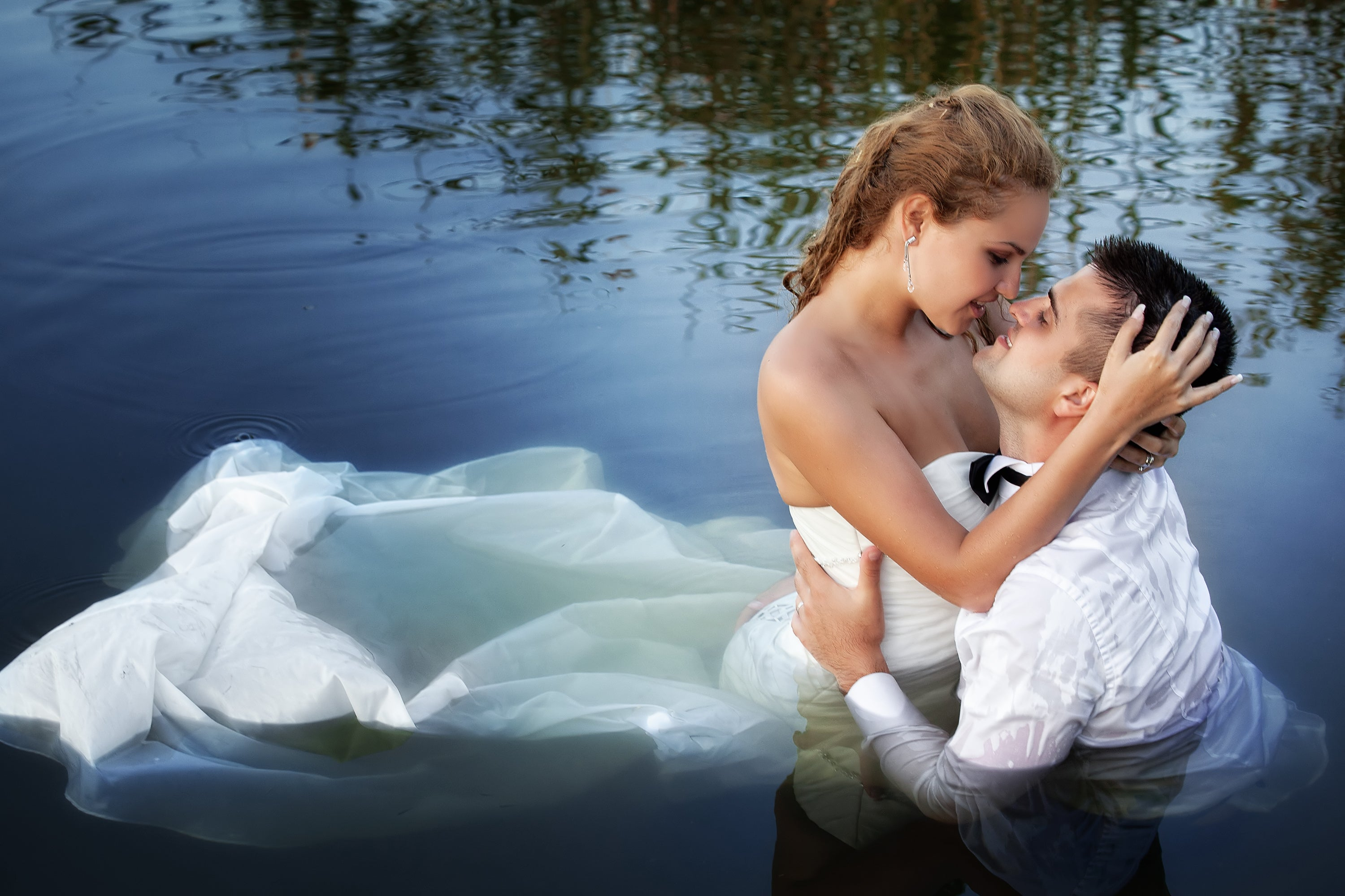 """Trash the Dress"" photo of married bride and groom kissing in the water"