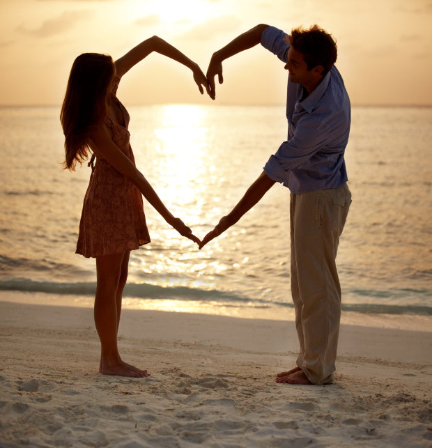 Man and woman on the beach at sunset making a heart with their joined arms
