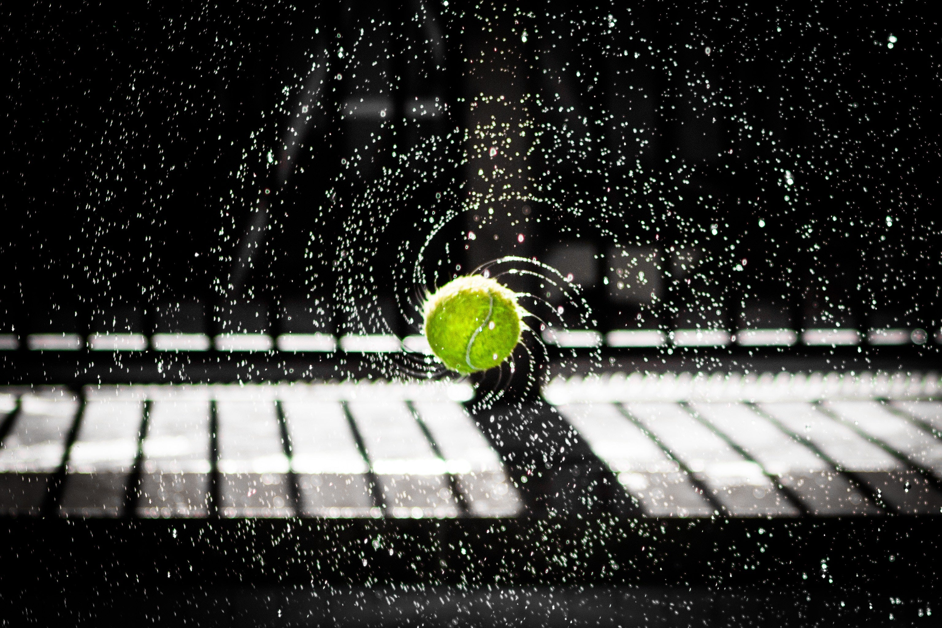 Water spraying from a tennis ball captured with a fast shutter speed