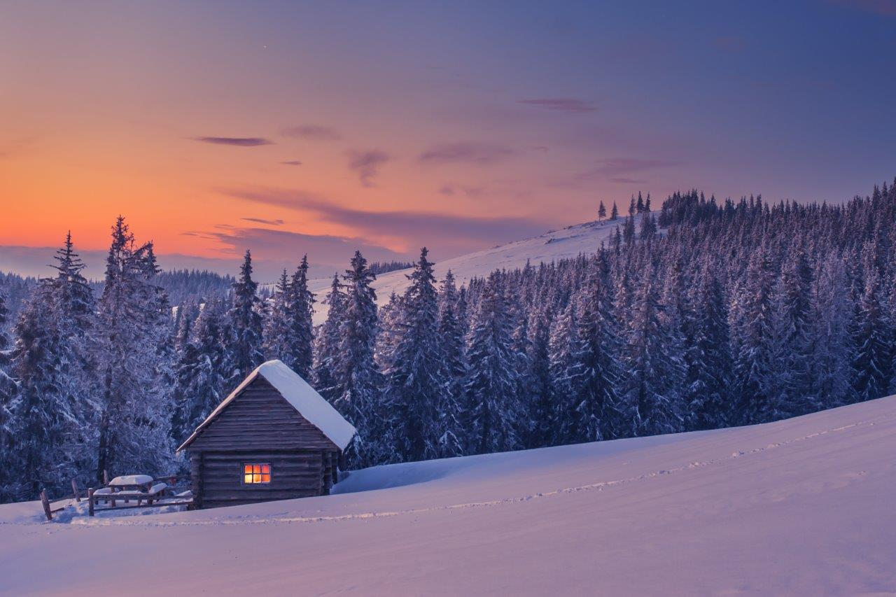 Snow-covered cabin in the mountains at dusk