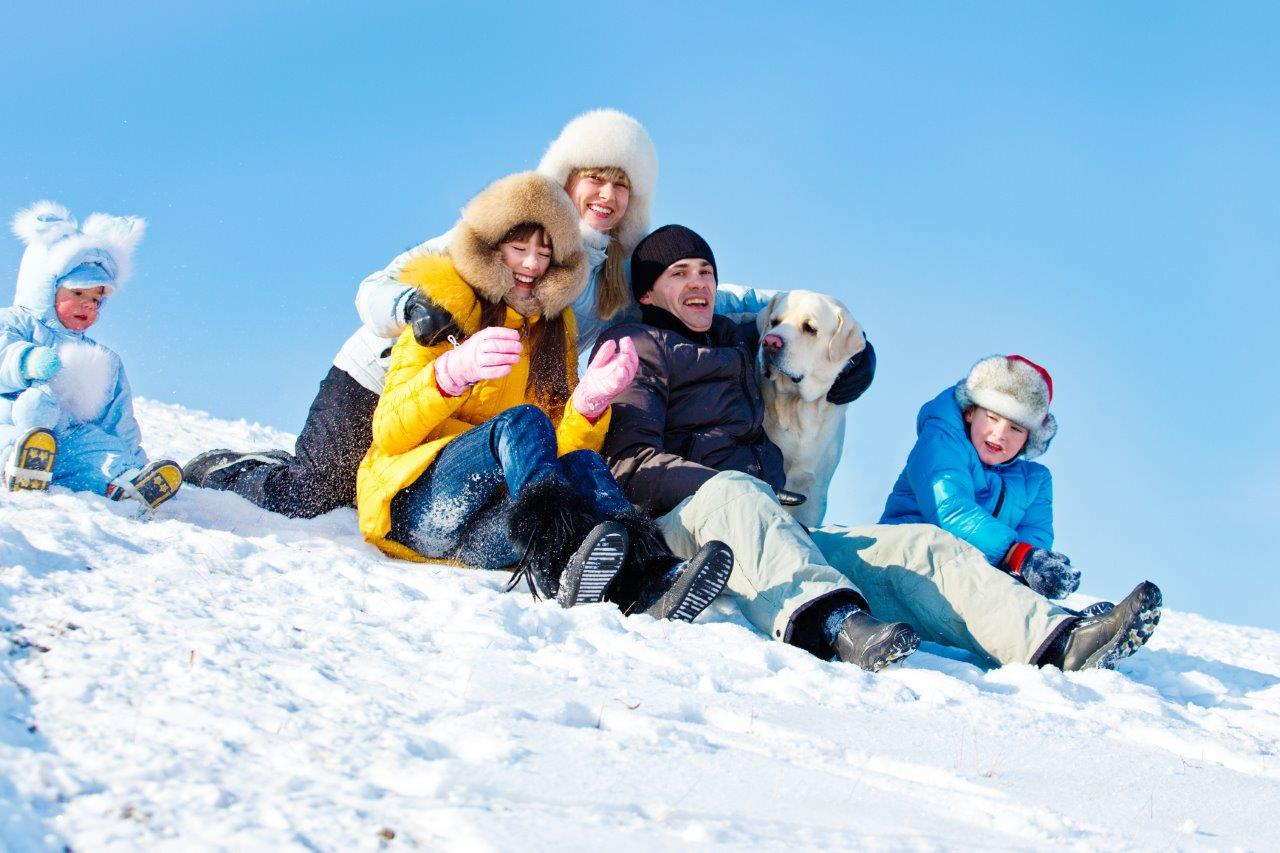 Winter holiday portrait of family and dog in the snow having fun