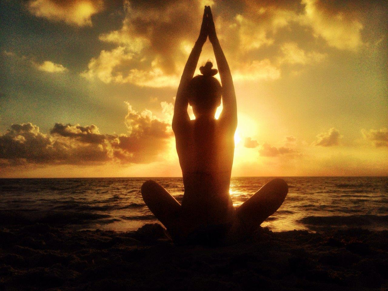 Silhouette of a person doing yoga on the beach at sunrise or sunset