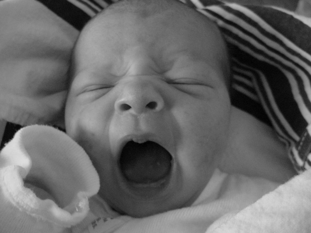 Black and white photo of a yawning newborn baby