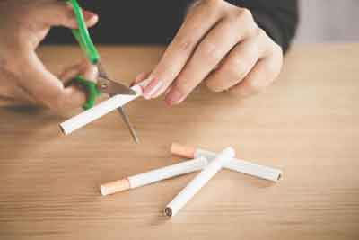Woman hand cut cigarette with scissors no smoking day