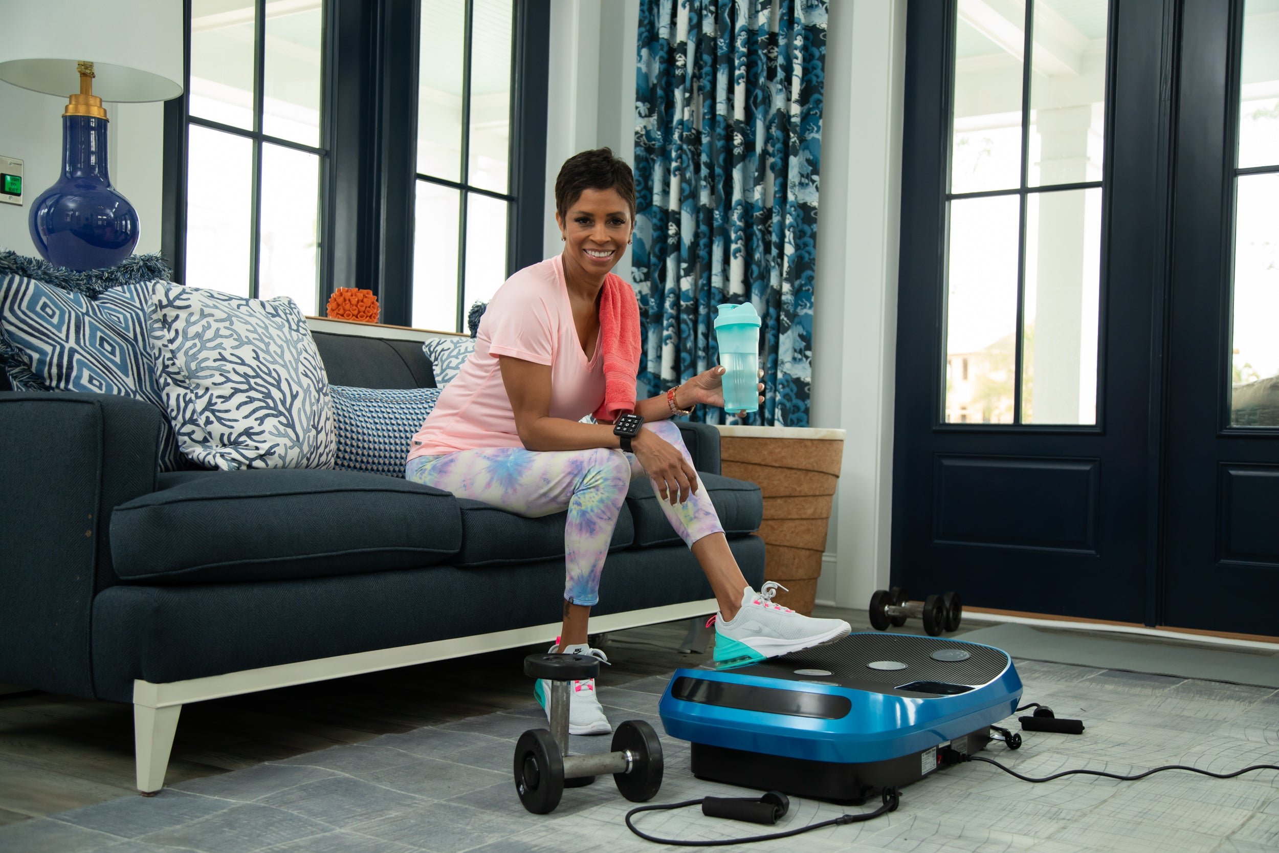 woman sitting on a couch drinking water next to a vibration plate and other exercise equipment