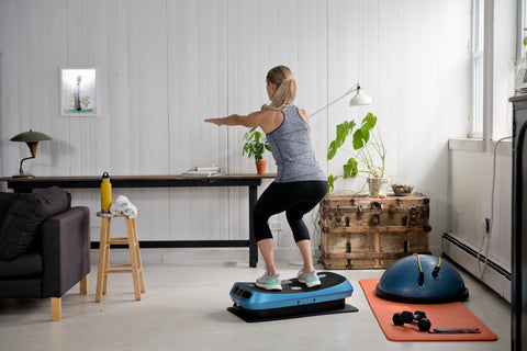 Woman Squat While Using Vibration Plate