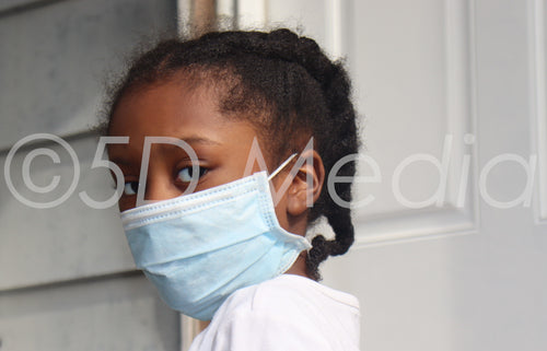 Girl Wearing surgical mask standing on house back porch with white door ( stock photo For Commercial & Editoral Use)