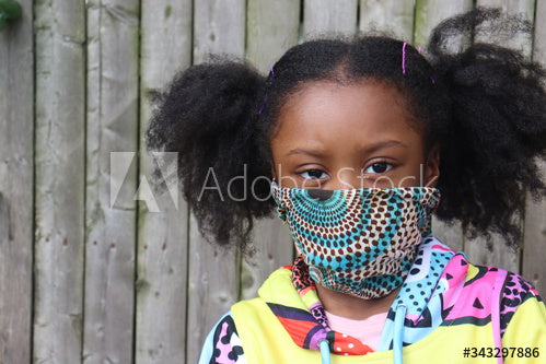 Cute African American Girl with pigtails wearing pattern fabric face mask outside with wooden fence background Stock Photo
