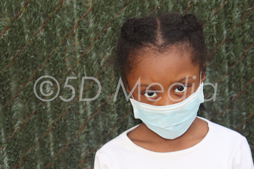 Young Girl Wearing Surgical Mask with green background Stock Photo