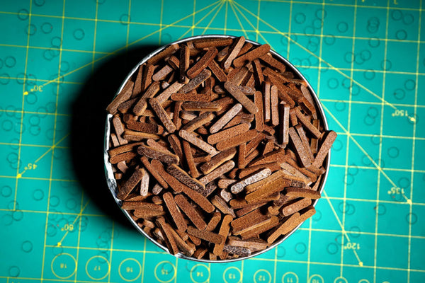 A bucket full of punched leather from making the Buffalo King guitar strap.