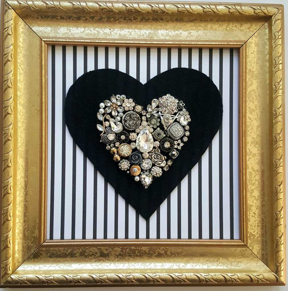 Handmade bejeweled heart created from vintafe jewelry mounted on a pinstripe background in a gold frame.