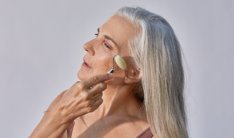 Woman with silver hair using jade roller tool on cheekbone