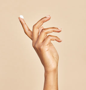 Model hand with eye cream on tip of index finger