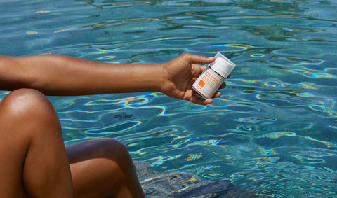 Model holding sunscreen against backdrop of clear blue water