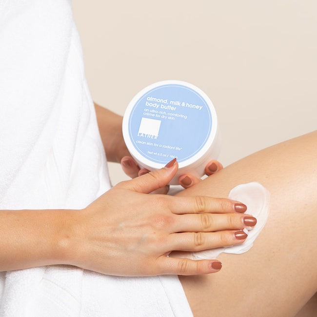 Women applying LATHER's almond, milk & honey body butter to leg