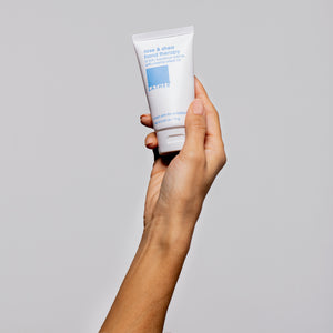 women holding rose and shea hand therapy cream in right hand