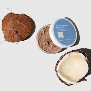 Open jar of Coconut Foaming Body Scrub next to a pieces of a cracked open raw coconut