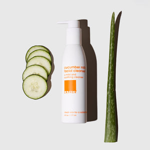 Cucumber Milk Facial Cleanser bottle next to slices of cucumber and a stalk of aloe vera
