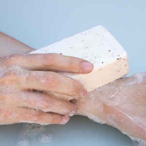 Close up of hands using sudsy Exfoliating Body Soap with Oatmeal & Bamboo Extract on forearm