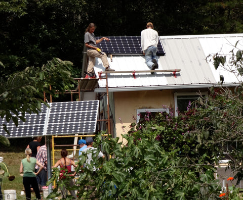 Two people on roof installing solar panels