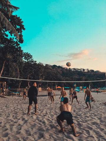 Group-Of-Friends-Playing-Beach-Volleyball-At-Sunset