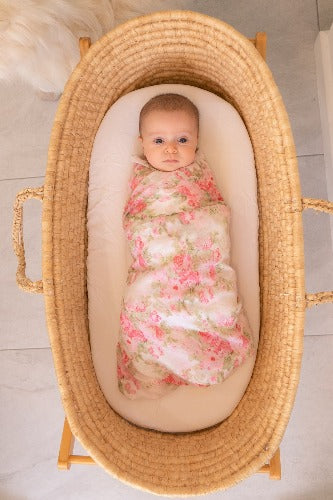 baby in basket swaddled in peony floral muslin