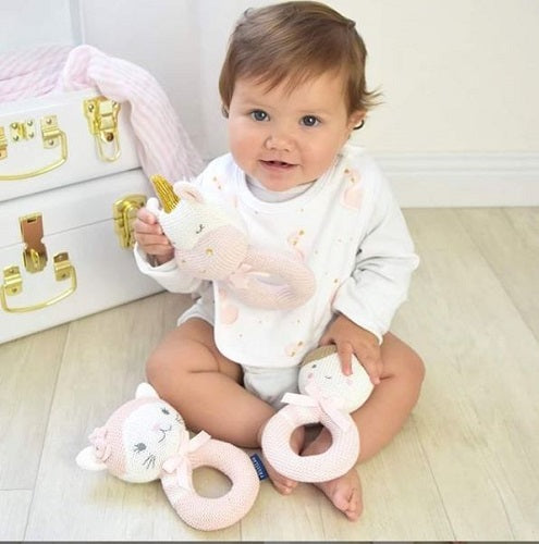 Baby with knitted ring rattles by Living Textiles