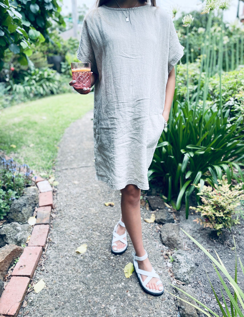 Woman walking through garden wearing the Eadie Lifestyle Pocket Linen Dress in natural
