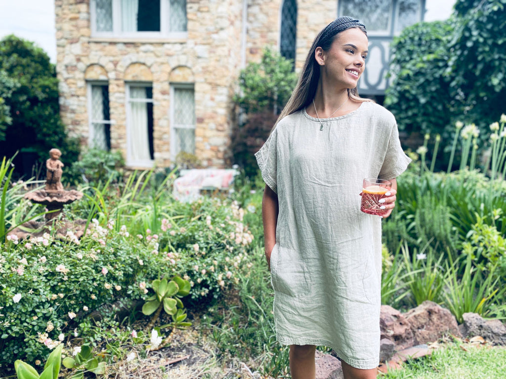 Woman standing in garden wearing the Eadie Lifestyle Pocket Linen Dress in natural