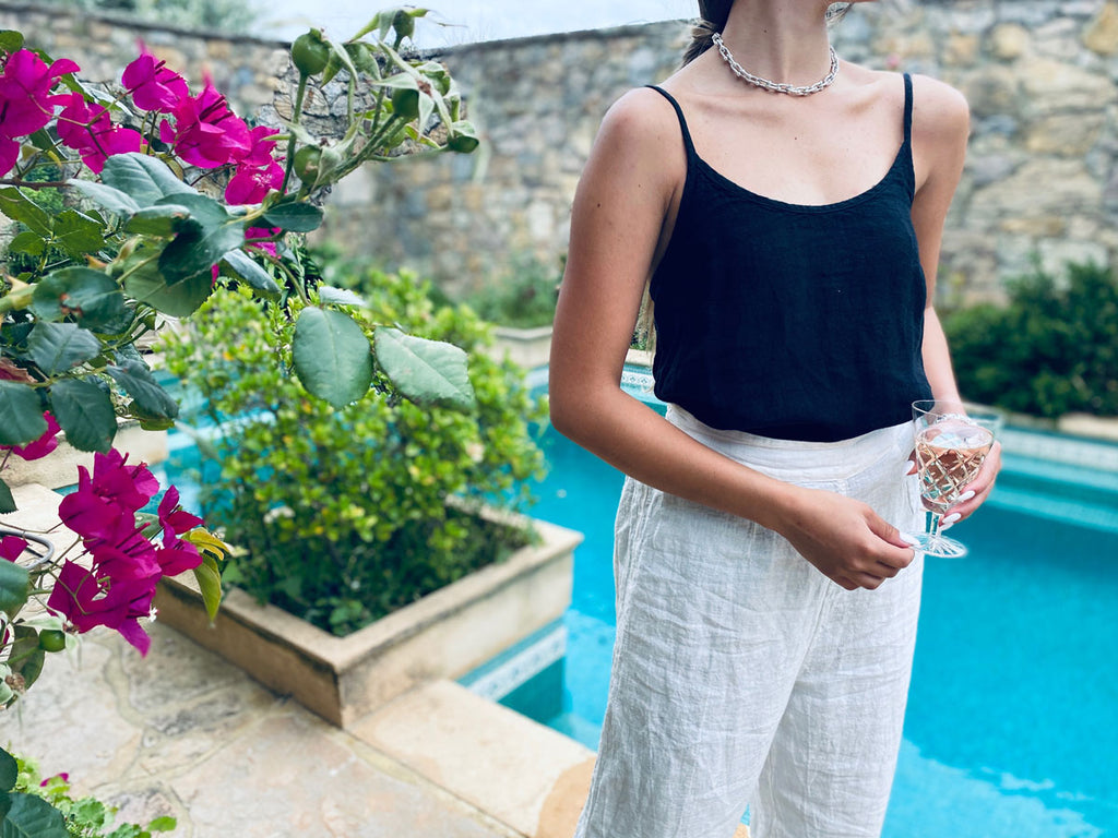 Woman wearing linen clothing standing in front of a pool