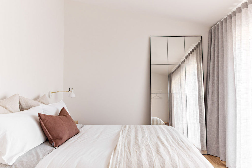One of the bedrooms at The Shore featuring our Luca Desert Rose cushion