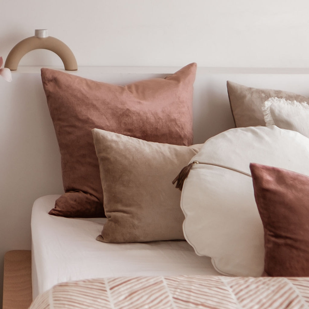 Velvet cushions in natural colours sitting on the bed