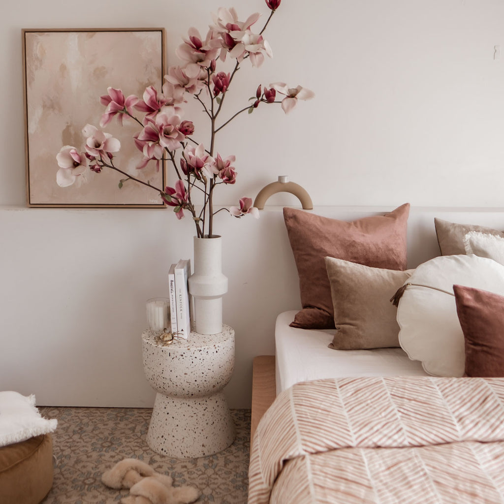 Spring bedroom with layered velvet cushions, stone terrazzo stool and Magnolia flowers