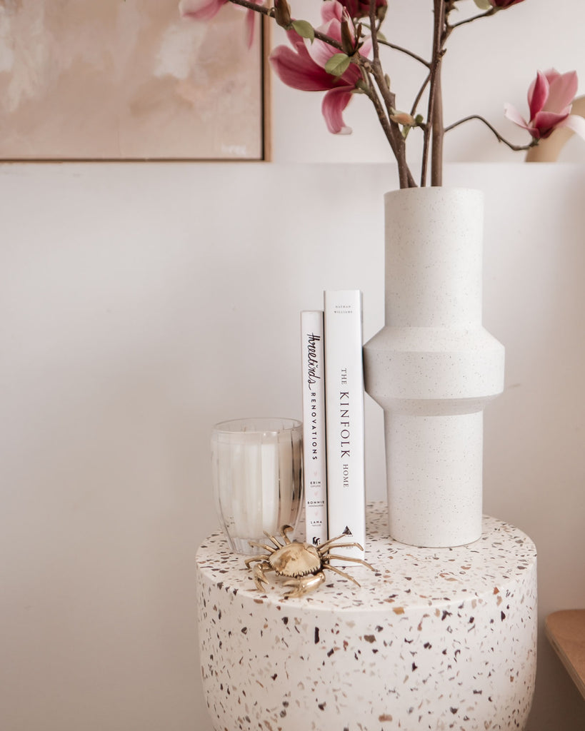 Some books and a vase filled with magnolias sit atop the terrazzo side table