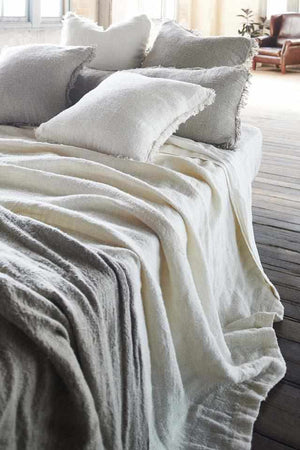 White Bedouin Oversized Linen Bed Throw layered with Bedouin Linen Cushions  on bed