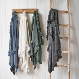 Chelsea throws in Navy, White, Khaki and Slate hanging on a rack