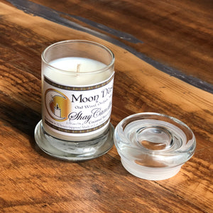 """Moon Dust"" is a powerfully scented candle that will take you on an intergalactic trip with its exotic Oud Wood, eerie Black Orchid and romantic ""Musk scents, in a sophisticated Elite Style Jar with a glass lid."