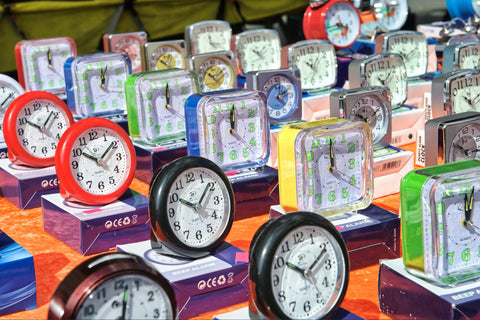 Multiple clocks on a desk to demonstrate reminders for habit tracking
