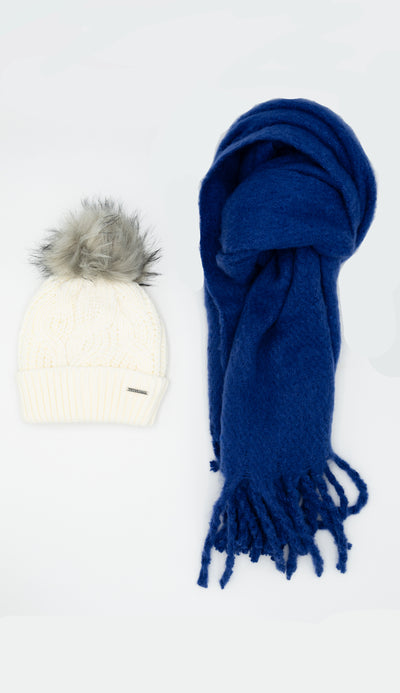 white knit hat with faux fur pom pom and sapphire chunky scarf