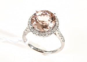 A MORGANITE AND DIAMOND CLUSTER RING - Centrally set with an oval faceted morganite of 5.06cts, surrounded and shouldered by diamonds totalling 0.50cts, mounted in 18ct white gold, ring size O.